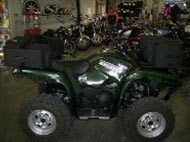 A green ATV in a workshop.